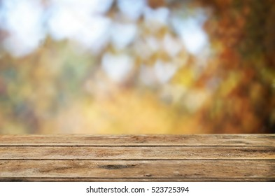 Autumn background with old wooden table and trees.