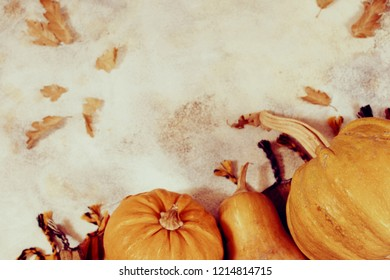 Autumn background with pumpkins overhead view with copy space and dry leaves