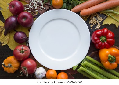 Autumn background with various vegetables around white empty dish with top view