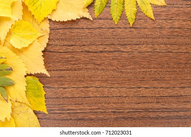 Autumn background. Yellow leaves on a wooden surface