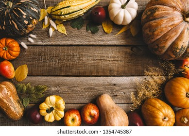 Autumn background with yellow leaves, red apples and pumpkins. Frame of fall harvest on aged wood with copy space. Mockup for seasonal offers. Top view.
