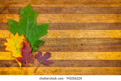 Autumn background with yellow and orange fall leaves on wooden serving board