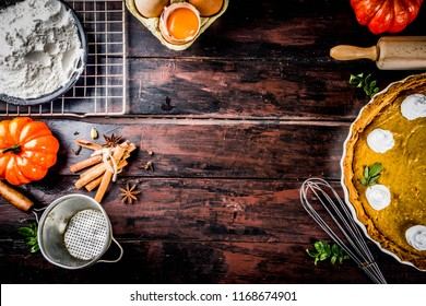 Autumn baking background, baking ingredients for pies, cookies - pumpkins, pumpkin pie, spices, flour, eggs, rolling pin, whisk, old wooden table top view copy space, with notebook for recipes