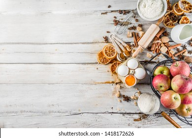 Autumn baking sale concept. Cooking seasonal fall baking background with ingredients, spices, apples, supplies, white wooden table top view copy space