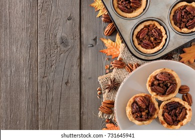 Autumn baking scene side border with pecan tarts, leaves and nuts over a wood background