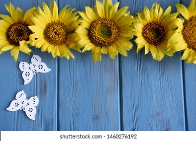 Autumn banner with flowers of sunflower on a blue wooden background. Frame for greeting card with flowers of sunflower. View from above