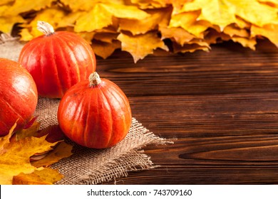 Autumn banner with yellow leaves and pumpkins on piece of sackcloth on a wooden textured backdrop. Fall background for thanksgiving day or seasonal sales card or flyer.