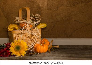 Autumn Basket A tabletop a basket of mini pumpkins and gourds, dried leaves, a sunflower, and red mums.