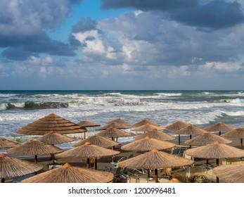 Autumn beach with straw beach umbrellas in Rethymno, Crete island, Greece