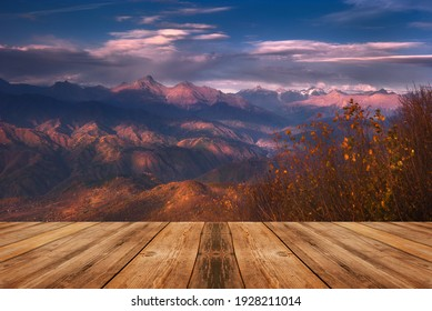 Autumn beautiful background. Mountains and empty wooden table in nature outdoor. Natural template landscape.