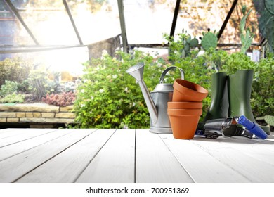 Autumn beautiful garden with white wooden table and garden tools
