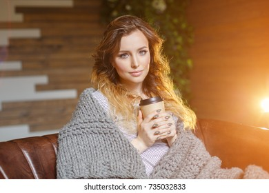 In autumn a beautiful young woman at home with a cozy rug