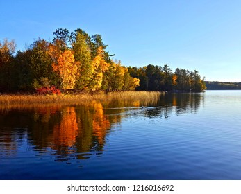 Autumn beauty on a lake in Northern Minnesota with red, orange and yellow trees reflecting on the calm blue water with blue sky