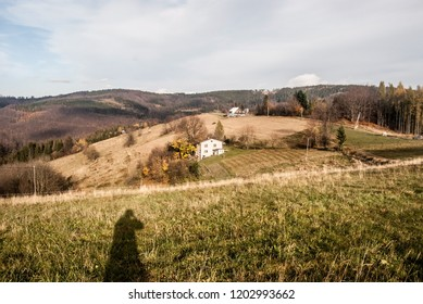 autumn bellow Filipka hill in Slezske Beskydy mountains in Czech republic with meadows, fes houses, hills, photographer shadow and blue sky with clouds