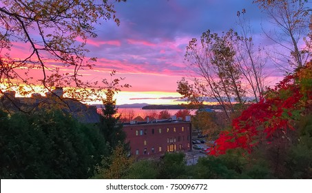 Autumn Blazed colors over looking Lake Champlain, Vermont in October.  Beautiful red foliage and pink sunset overlooking the lake  with a building in the forefront.