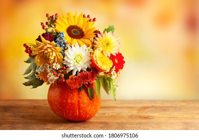Autumn bouquet of beautiful flowers and berries in a pumpkin on wooden  table. Concept of autumn festive decoration for Thanksgiving day.