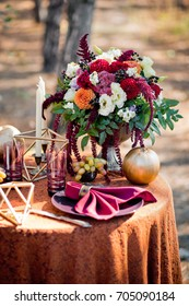 Autumn bouquet with dahlias on the served table in the wood