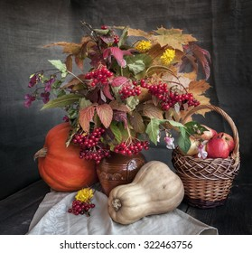 The autumn bouquet of leaves, flowers and berries in a clay vase, apples in the basket and pumpkins on a wooden table
