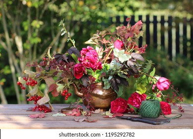 Autumn bouquet in vintage cooper teapot, kettle, rustic secateurs, sisal twine on aged table, fence background, natural light, outdoor and space