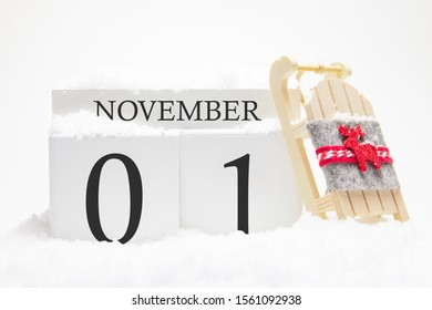 Autumn calendar made of wooden cubes with the date of November 1, the concept of the first snow and future holidays. Close-up.