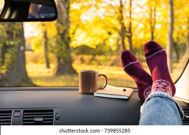 Autumn car trip. Woman feet in warm wool socks and cup of tea in the car