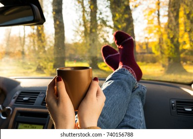 Autumn car trip. Woman feet in warm wool socks and cup of tea in the car. Freedom concept