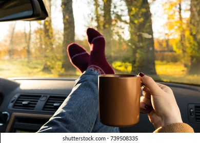 Autumn car trip. Woman in warm wool socks and cup of tea in the car
