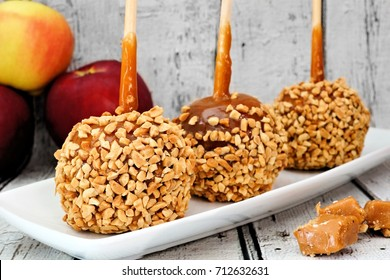 Autumn caramel apples with nuts on a plate with rustic white wood background