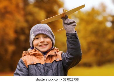 autumn, childhood, dream, leisure and people concept - happy little boy playing with wooden toy plane outdoors