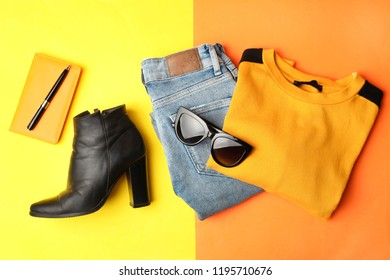Autumn clothes and boots on orange background.