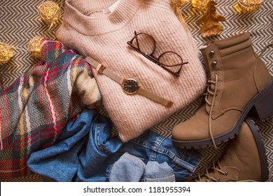 Herbstkleidung mit Pullover, Jeans und Stiefeln, Draufsicht von Herbst/Winter-Outfit Idee mit Brille und Uhrenzubehör