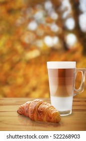 Autumn coffee with croissant on wooden table.