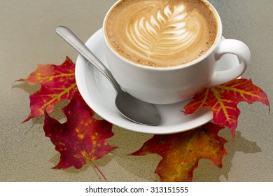 Autumn Coffee Latte with Orange and Red Fall Leaves. A hot latte with a design in the foam sits on a white plate with a spoon on a glass table with red, orange, and yellow autumn fallen leaves at cafe