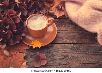 Autumn. Coffee on an old battered table with autumn flowers and maple leaves. Cozy autumn background in chocolate tones.
