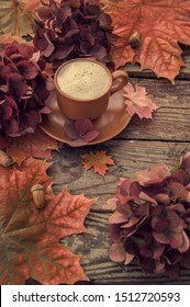 Autumn. Coffee on an old battered table with autumn flowers and maple leaves. Cozy autumn background in chocolate tones. Autumn background top view.