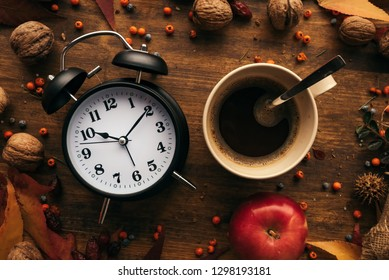 Autumn coffee time, top view flat lay of vintage alarm clock with cup of hot coffee on a table decorated with autumnal fruit and dry maple leaves