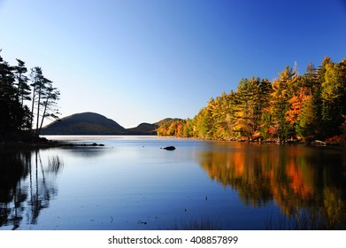 autumn colorful forest reflecting in tranquil lake in the morning