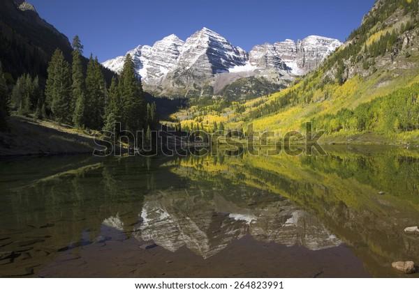 Autumn colors of Aspens reflecting in lake under Maroon Bells, Colorado, near Aspen