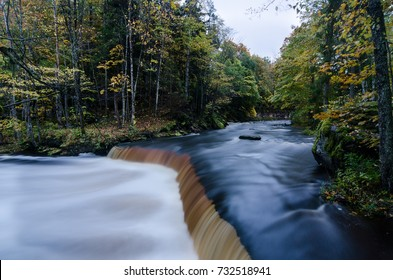 Autumn colors by the Nommeveski waterfall (cascade) on the river Valgejogi in Lahemaa National Park, Estonia. Long exposure brings good motion effect to the river.