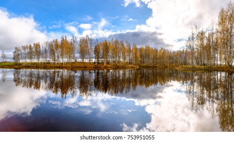 Autumn coloured trees with reflection in water, blue sky in background.