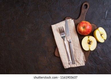autumn composition with copy space of kitchen utensils. Cutting board, knife and fork on dark background