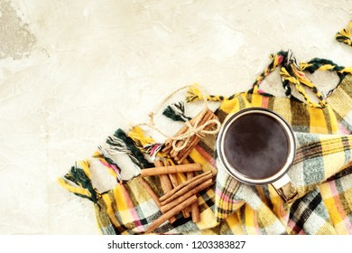Autumn composition. Cup of coffee, blanket, autumn leaves, cinnamon sticks on beige background. Flat lay, top view.