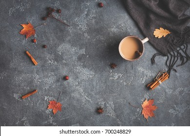 Autumn composition. Cup of coffee, blanket, autumn leaves, cinnamon sticks on black background. Flat lay, top view.