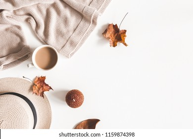 Autumn composition. Cup of coffee, hat, dried autumn leaves, beige sweater on white background. Flat lay, top view, copy space