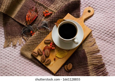 Autumn composition of a cup of coffee, a warm scarf, fallen leaves, cookies in the form of coffee beans