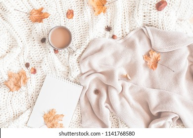 Autumn composition. Cup of coffee, women fashion sweater, dried leaves, plaid, notebook. Autumn, fall concept. Flat lay, top view, copy space