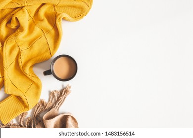 Autumn composition. Cup of coffee, yellow sweater, plaid on white background. Autumn, fall concept. Flat lay, top view, copy space