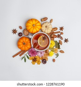 Autumn composition. A cup of fragrant tea surrounded by dry leaves, nuts, flovers and pumpkins