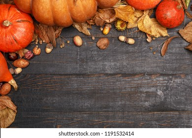 Autumn composition with dry leaves and ripe pumpkins on a dark wooden table. Top view. Copy space