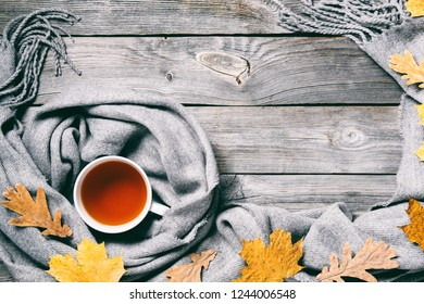 Autumn composition, fall leaves, hot steaming cup of tea and a warm scarf on wooden table background. Retro toning.